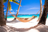 Fototapety Straw hammock in the shadow of palm on tropical beach by sea