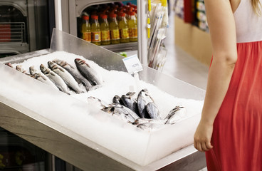 Woman shopping for fish in a supermarket