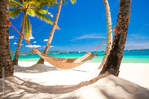 Straw hammock in the shadow of palm on tropical beach by sea - 60724010