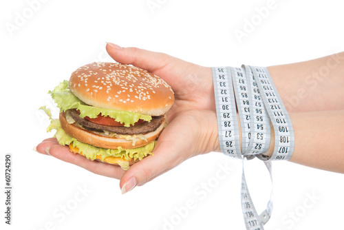 Burger cheeseburger in hands with measure tape