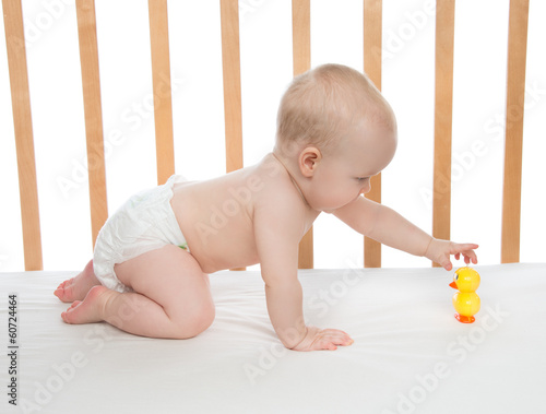 little child baby girl crawling in bed with toy duck