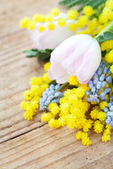 Spring flowers: mimosa, tulips and muscari on wooden background