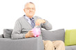Middle aged man seated on sofa putting money into piggybank