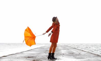 Broken Orange umbrella fly from the girl.
