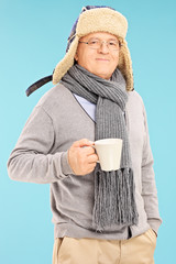 Senior man with winter hat holding a cup