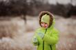 boy in a green suit walks in the park in winter with frozen tree