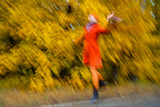 Girl in orange coat running in the yellow autumn forest.