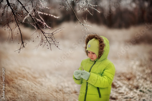 boy in a green suit walks in the park in winter with frozen tree
