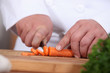 closeup of a cook cutting carrots