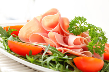Sliced ham with arugula leaves and tomatoes