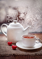 tea cup and  teapot with red hearts   in winter frosty day