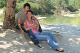 Young couple sitting by a lake