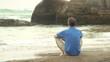 Mann sitzt auf Fels am Meer
