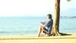 Mann liest angelehnt an einen Baum ein Buch am Strand