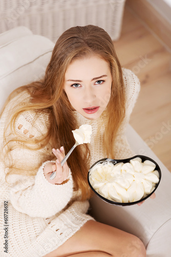 Beautiful caucasian sad woman eating ice creams.