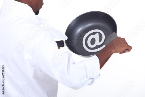 Afro-American chef drawing the at sign on a frying pan