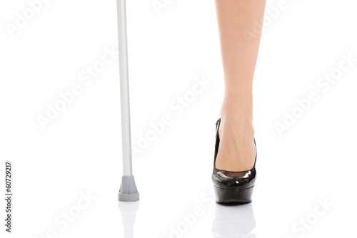Woman's leg and a crutch. Disabled concept.