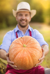 Gardener with huge pumpkin