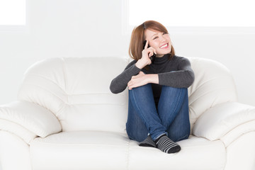 ソファで電話をする女性