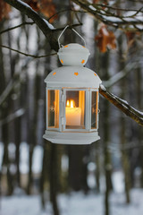 White lantern hanging on fir branch in forest. Beautiful winter
