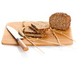 Fresh bread being sliced on a wooden cutting board with a bread
