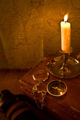 Burning candle and the compass on the old map background