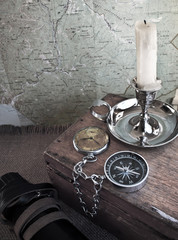 Compass and candle on the background of old maps