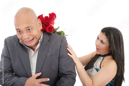 Woman striking his boysfriend with a bouquet of red roses.  Focu