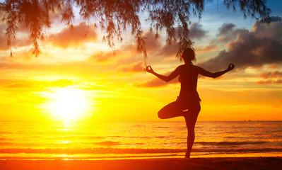Silhouette of woman meditating on the beach. Yoga and fitness.