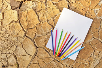 paper with color pencil on cracked earth