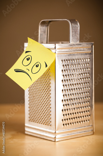 Post-it note with smiley face sticked on grater