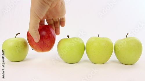 Hand chooses a red apple from a line with green apples