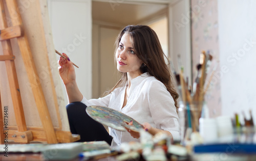 woman paints picture on canvas in her studio
