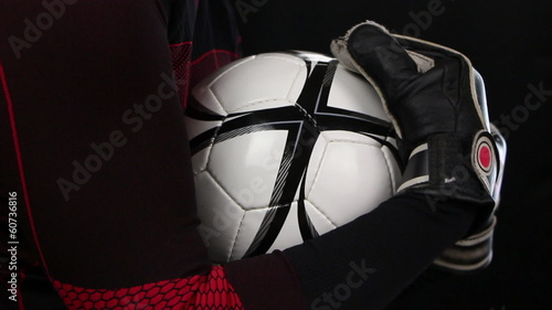 Football, soccer goalkeeper grips a ball, close up