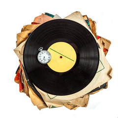 Stack of old scratched dusty vinyl records and pocket watch