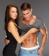 Young woman embracing man with naked muscular torso