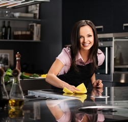 Young cheerful woman cleaning modern kitchen