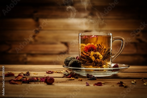 Glass cup with tea flower against wooden background