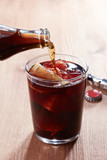 Pouring cola into kalimotxo mixture glass