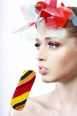 Портрет девушки с ярким макияж и конфетой на белом фоне