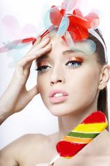 ортрет девушки с ярким макияж и конфетой на белом фоне