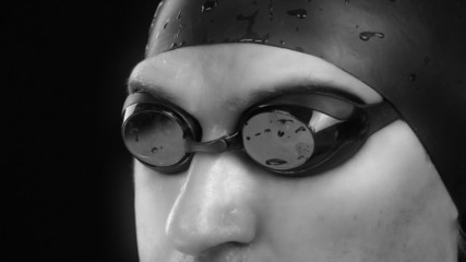 Swimmer concentrates and prepares for a start,with water drops