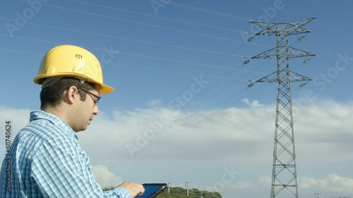 Electrical engineer in front of a power line. Tablet.