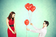 Man approaching woman giving her red heart shape balloons