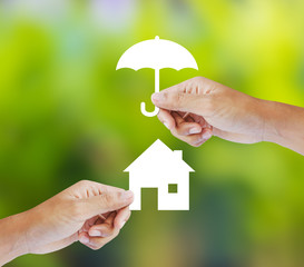 Hand holding a paper home and umbrella on green background
