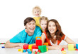 Happy family four persons. Smiling kids playing toys blocks