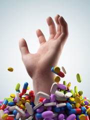 a hand breaching through a lot of pills