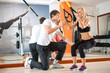 girl doing squats with the help of trainer