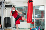 Man practicing some kicks with a punching bag
