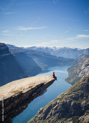 man sitting on trolltunga rock in norway